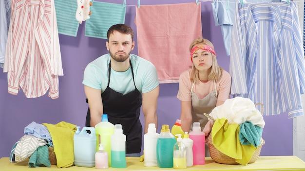 Man en vrouw zijn de huishoudelijke taken beu. gewassen kleding hangt aan wasknijpers