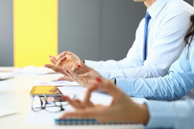 Man en vrouw zitten aan tafel in kantoor en mediteren.