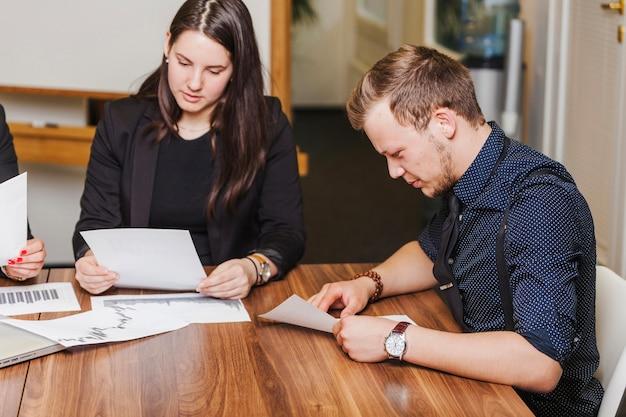 Man en vrouw zitten bij het lezen van een bureau