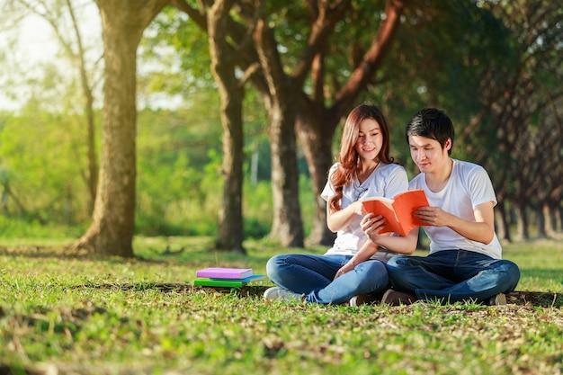 Man en vrouw zitten en lezen van een boek in het park