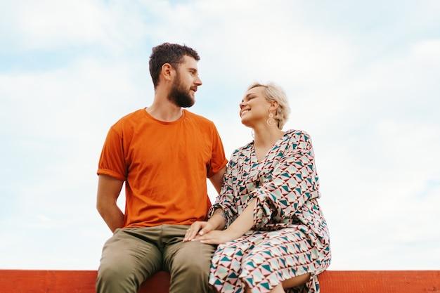 Man en vrouw zitten gelukkig op een houten plank op zoek naar elkaar lachend in de lucht