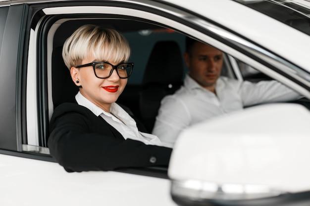 Man en vrouw zitten in een autosalon. close-upportret van vrouw het kijken uit een venster.