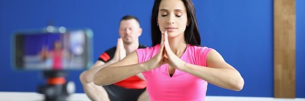 Man en vrouw zitten in lotushouding op gymnastiekmatten voor de camera