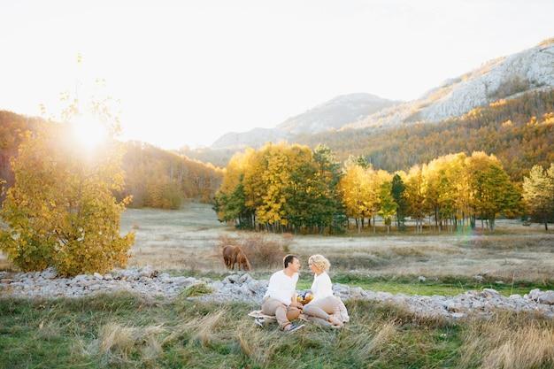 Man en vrouw zitten op een deken op een grasveld midden in een herfstbos