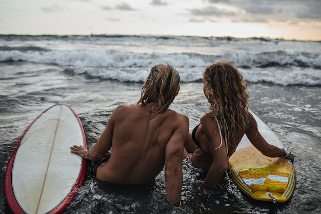 Man en vrouw zittend op het strand met surfplanken