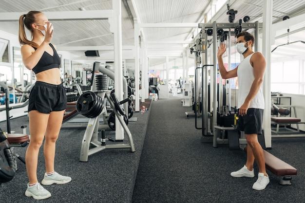Man en vrouw zwaaien naar elkaar in de sportschool