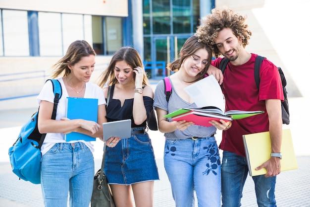 Man en vrouwen die bij universitaire campus bestuderen