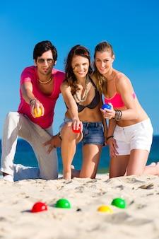 Man en vrouwen die boule op strand spelen