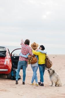Man en vrouwen die dichtbij auto en hond op overzees strand omhelzen