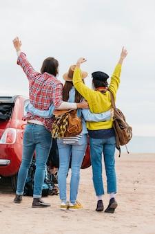 Man en vrouwen die dichtbij auto op overzees strand omhelzen