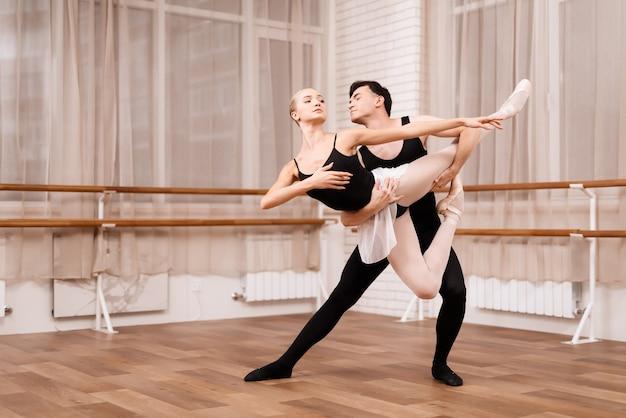 Man en vrouwendansers die in balletklasse stellen.