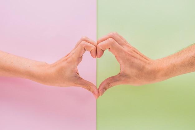 Man en vrouwenhanden die symbool van hart tonen