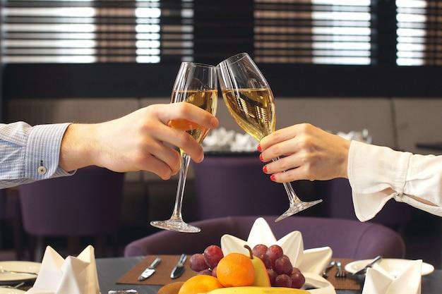 Man en vrouwenholdingsglazen met wijn in restaurant