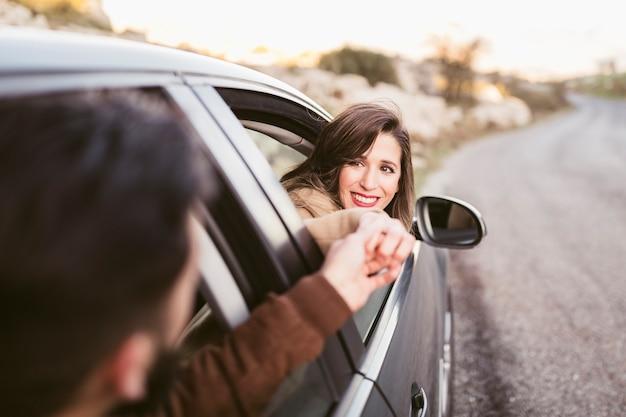 Man en vrouwenholdingshanden buiten auto