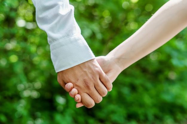 Man en vrouwenholdingshanden op een groene aard