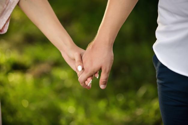 Man en vrouwenholdingshanden op groene achtergrond. heteroseksueel verliefde paar.