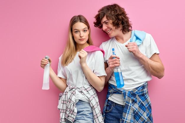 Man en vrouwenreinigers met sprays voor het schoonmaken geïsoleerd over roze studioachtergrond.