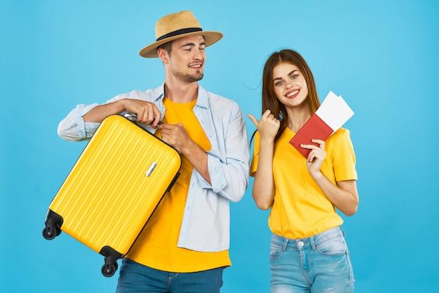 Man en vrouwenreiziger met een koffer, een gekleurde ruimte, vreugde, paspoort