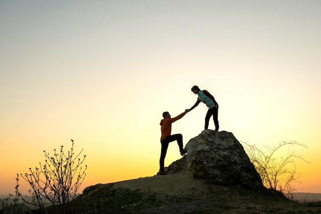 Man en vrouwenwandelaars die elkaar helpen om een grote steen te beklimmen bij zonsondergang in bergen. paar klimmen op een hoge rots in de avond de natuur. toerisme, reizen en een gezonde levensstijl concept.
