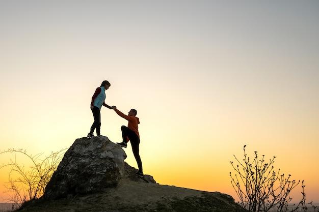 Man en vrouwenwandelaars die elkaar helpen om een grote steen te beklimmen bij zonsondergang in bergen. paar klimmen op een hoge rots in de natuur van de avond. toerisme, reizen en een gezonde levensstijl concept.