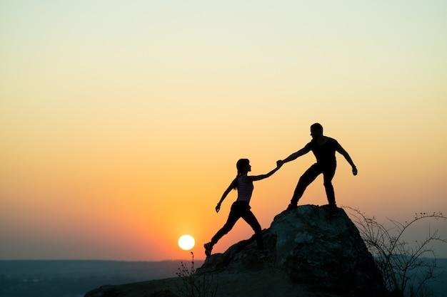 Man en vrouwenwandelaars die elkaar helpen om een grote steen te beklimmen bij zonsondergang in bergen