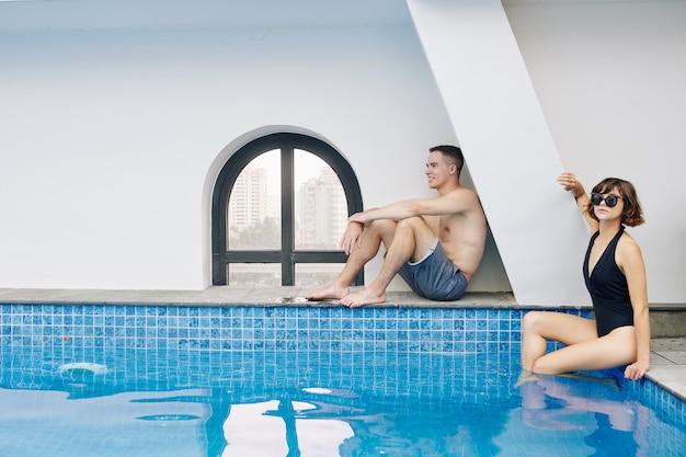Man en vrouwenzitting bij zwembad