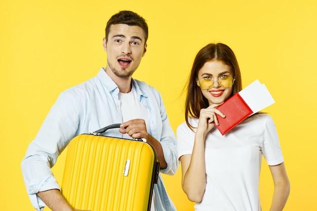 Man en vrouwreiziger met een koffer, gekleurde achtergrond, vreugde, paspoort