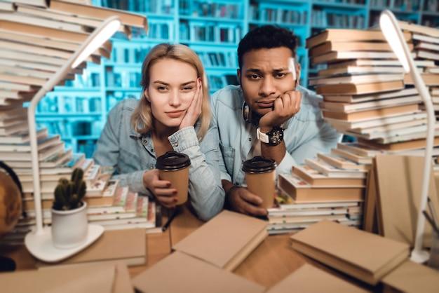 Man en witte meisjeszitting bij lijst die door boeken wordt omringd.