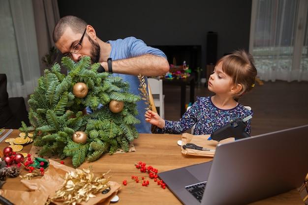 Man en zijn dochtertje leren een kerstkrans te versieren, kijk online les