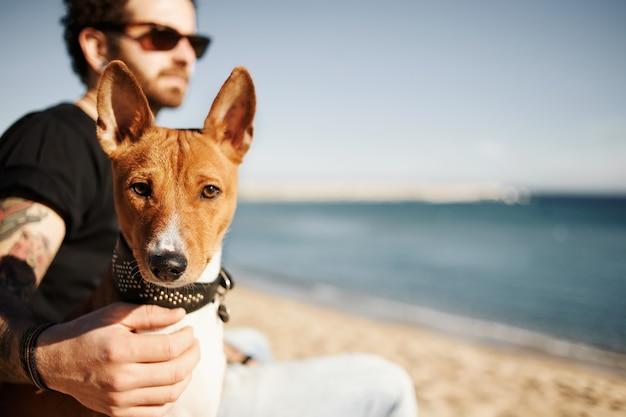 Man en zijn hond op het strand die de zee bewonderen