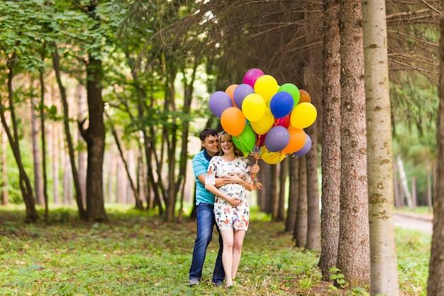 Man en zijn zwangere vrouw met ballonnen buitenshuis