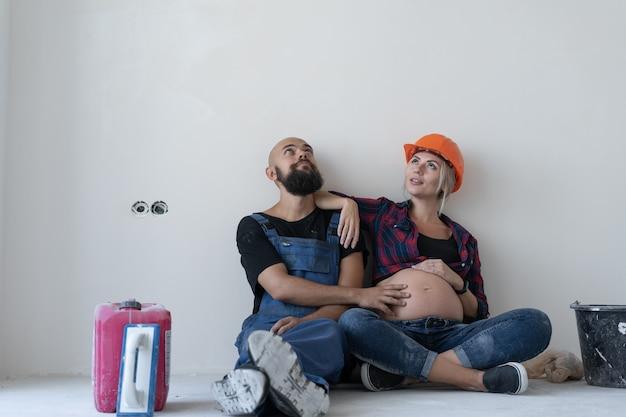 Man en zijn zwangere vrouw zitten op de vloer in de kamer. werkuniform en oranje veiligheidshelm. de buik strelen en omhoog kijken naar de lege ruimte.