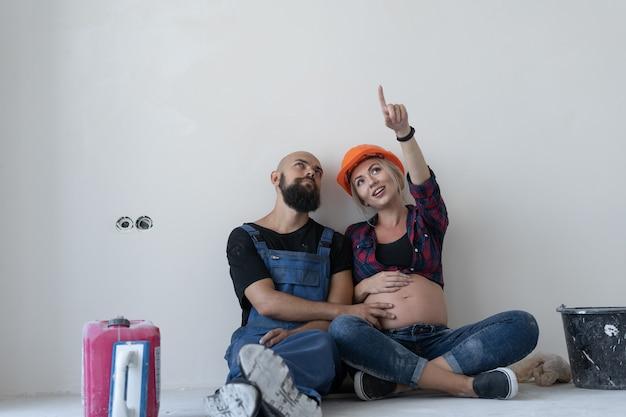 Man en zijn zwangere vrouw zitten op de vloer in de kamer. werkuniform en oranje veiligheidshelm. wijs omhoog en kijk naar vrije ruimte voor tekst.