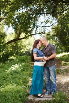 Man en zwangere vrouw, die in park in openlucht omhelzen