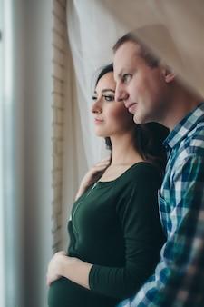 Man en zwangere vrouw die lacht door het raam kijkt
