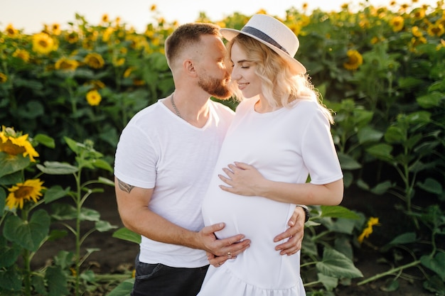 Man en zwangere vrouw omhelzen elkaar tedere staande in het veld met hoge zonnebloemen om hen heen