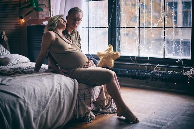 Man en zwangere vrouw zittend op het bed in loft-stijl kamer