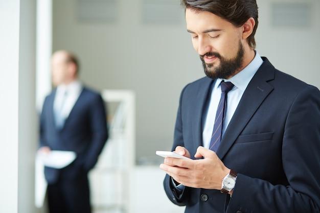 Man executive met behulp van zijn mobiele telefoon