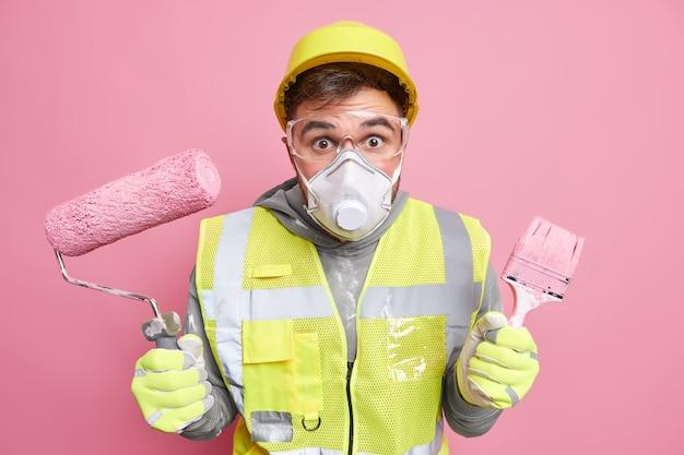 Man fabrieksarbeider draagt beschermende gasmasker veiligheidsbril houdt reparatiegereedschappen die iets gaan opknappen