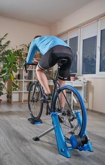 Man fietsen op de trainer tijdens het sporten thuis