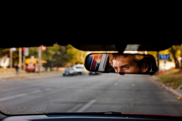 Man figuur gezien in man silhouet wassen van een achteruitkijkspiegel