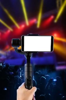 Man filmt met een leeg scherm smartphone met behulp van een cardanische stabilisator, geïsoleerd op muziekshow. selectieve aandacht.