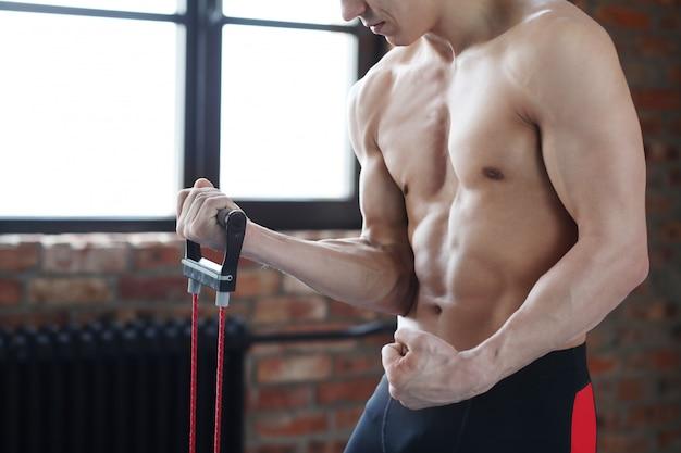 Man fitnesstraining. shirtless mens die thuis het uitrekken doen zich