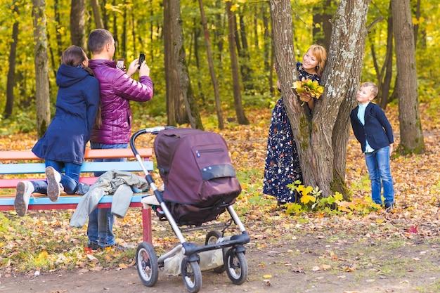 Man fotograaf zijn familie buiten in de herfst natuur
