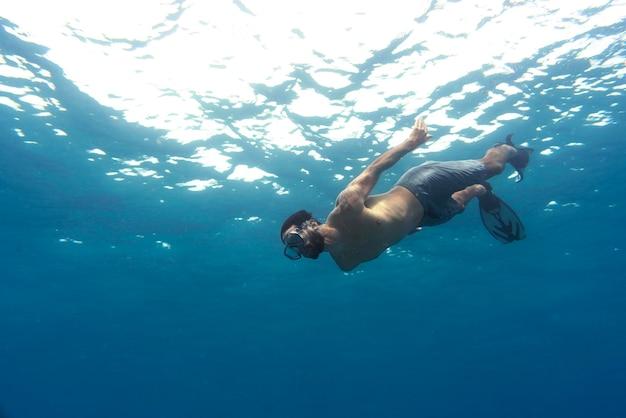 Man freediving met zwemvliezen onder water