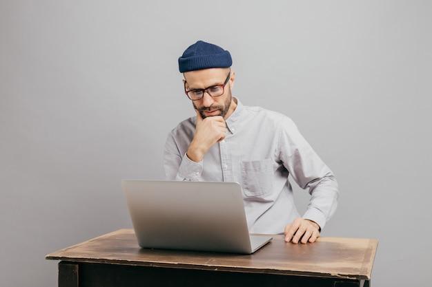 Man freelancer leest nieuws in internet, kijkt aandachtig naar een laptop computer