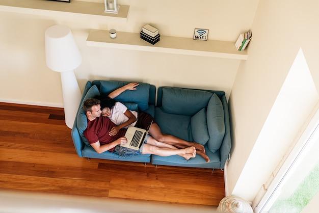 Man freelancer op bank met tevreden vriendin thuis