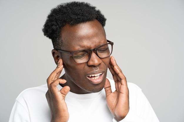 Man fronsend lijden aan tinnitus kloppende oorpijn moe van lawaai aanraken van pijnlijk oor Premium Foto