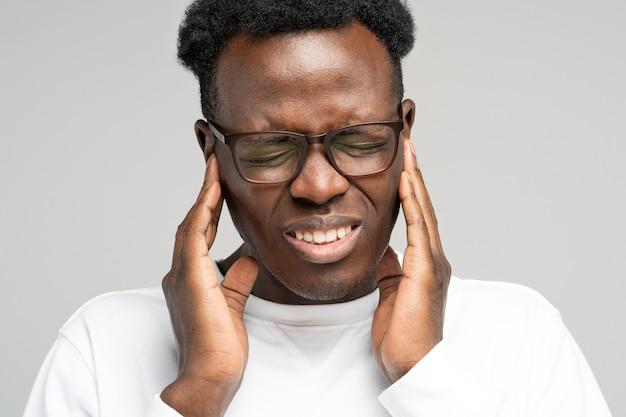 Man fronsend lijden aan tinnitus kloppende oorpijn moe van lawaai aanraken van pijnlijk oor