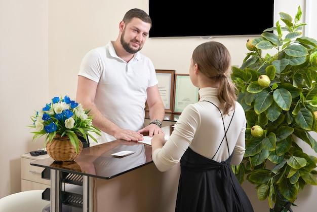 Man gastvrije jonge vrouw client bij de receptie van het kantoor